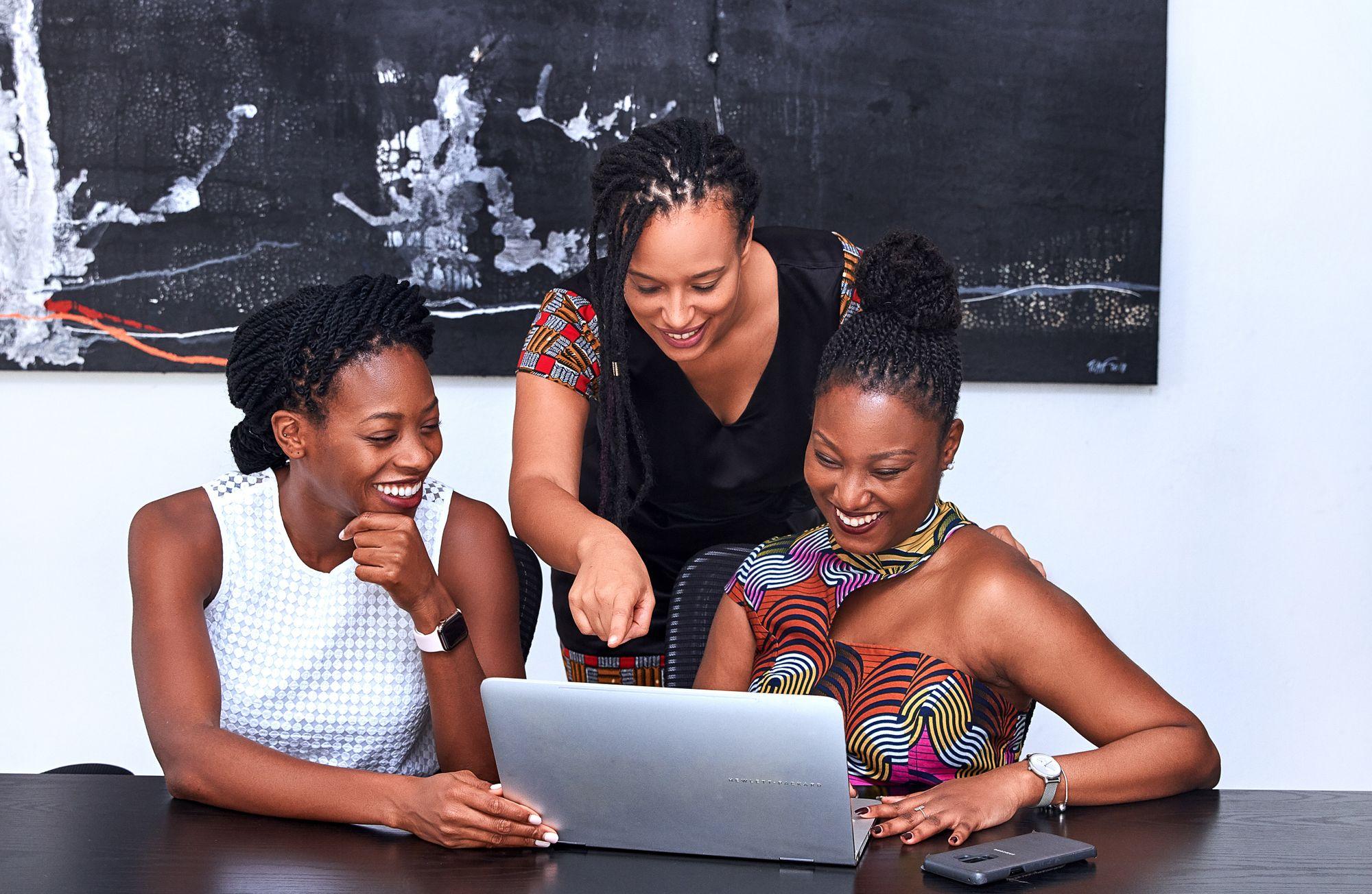 Três mulheres sorriem enquanto olham para notebook apoiado em mesa escura para ilustrar escolha por site de vaquinha. A primeira está sentada à esquerda e é negra de pele escura, com cabelo trançado preto para trás, usa vestido branco e olha para o notebook branco à sua frente. A segunda está em pé, é negra de pele clara, usa cabelo trançado solto, usa vestido preto com mangas vermelhas e aponta para a tela do mesmo notebook enquanto sorri. A terceira está sentada à esquerda, é negra de pele escura, com cabelo estilo coque, usa vestido de estampa colorida e sorri enquanto digita no mesmo notebook. O fundo é neutro, com parede branca e quadro preto.