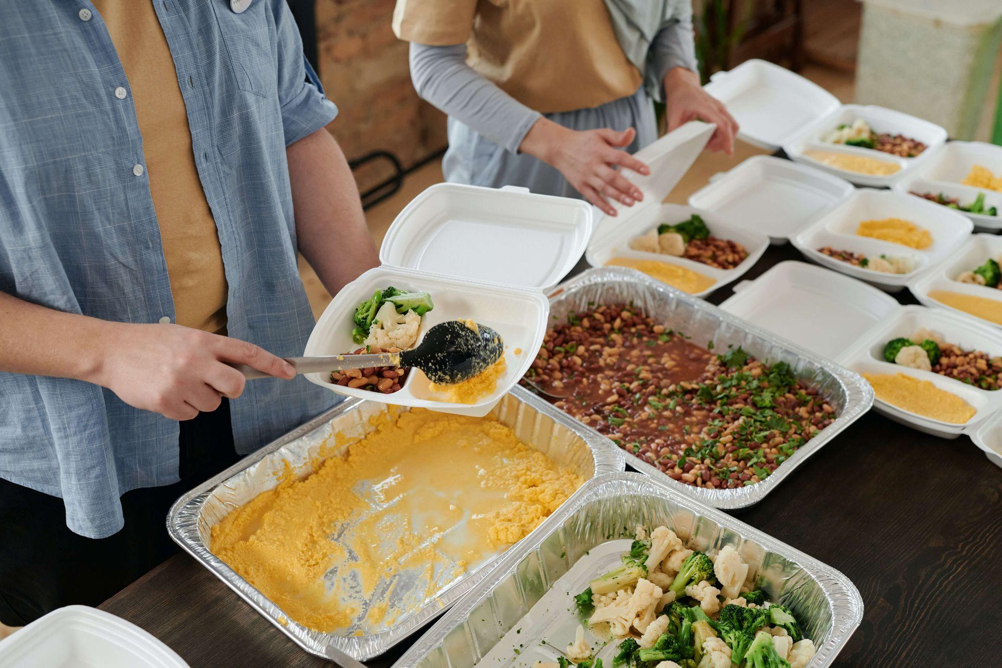 A imagem mostra duas pessoas próximas a uma mesa onde há diversos recipientes descartáveis com alimentos preparados. Elas montam marmitas de isopor com os alimentos.