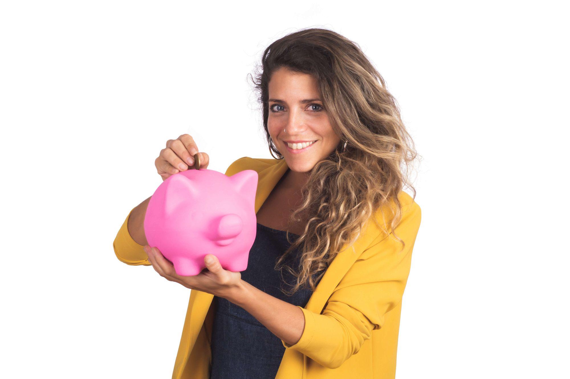 Mulher jovem colocando uma moeda em um cofrinho em formato de porco.