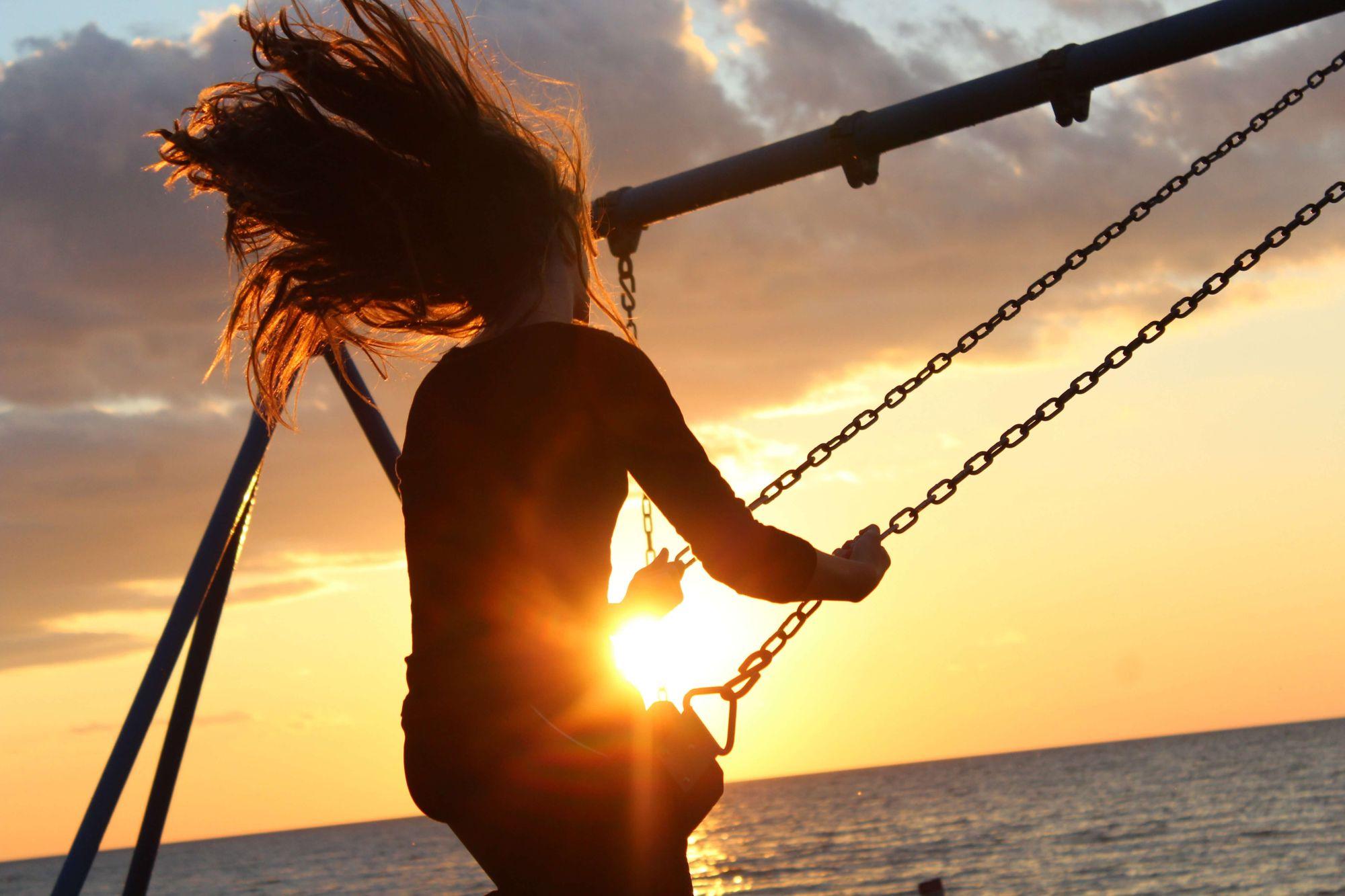 Jovem andando de balanço, com os cabelos ao vento, em frente ao por do sol no mar.