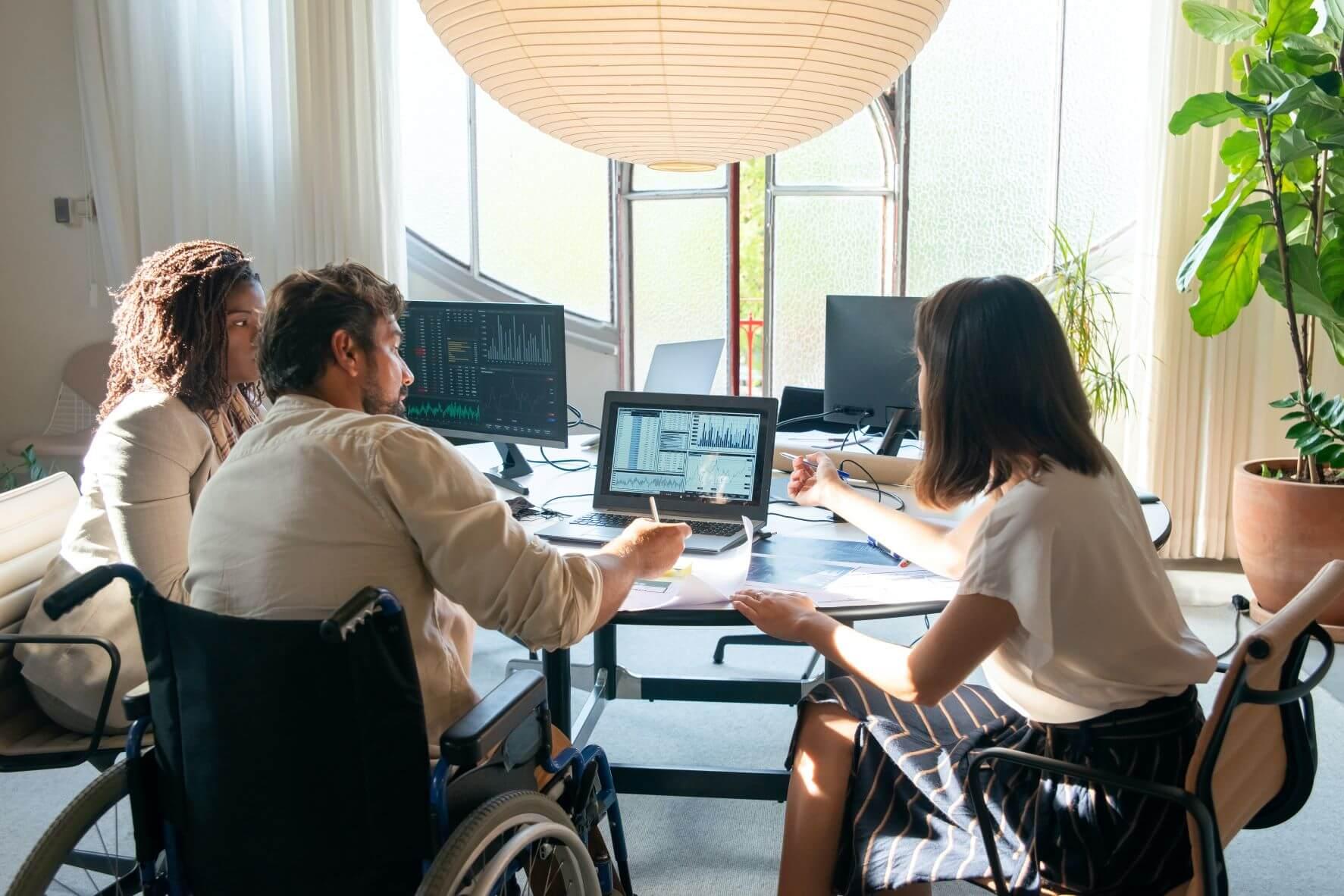 Foto de três pessoas sentadas diante de mesa com computadores e papéis em ambiente de escritório iluminado. A pessoa à esquerda é uma mulher negra, com cabelos longos pretos e roupa branca. Ao meio, está um homem branco, de cabelo e barba escuros curtos, que usa camisa social branca e está em cadeira de rodas. Na direita, uma mulher branca, de cabelo castanho escuro e roupa social