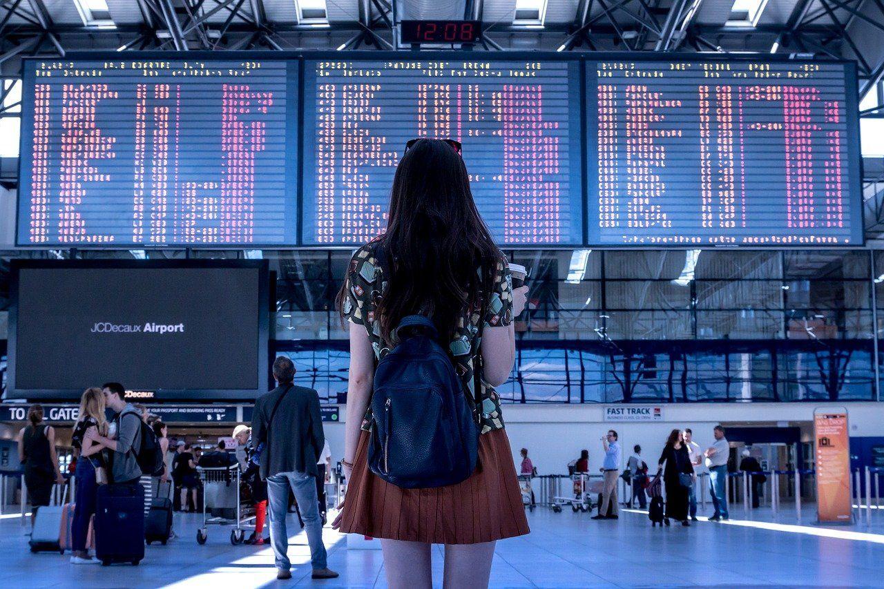 Menina de costas com mochila no aeroporto olhando para a tela de embarque