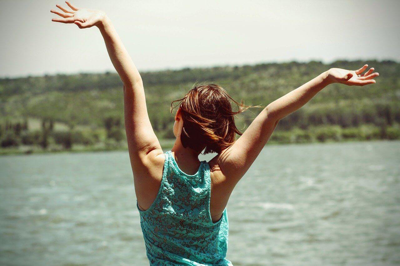 Mulher de costas e braços abertos em frente a um lago comemorando.