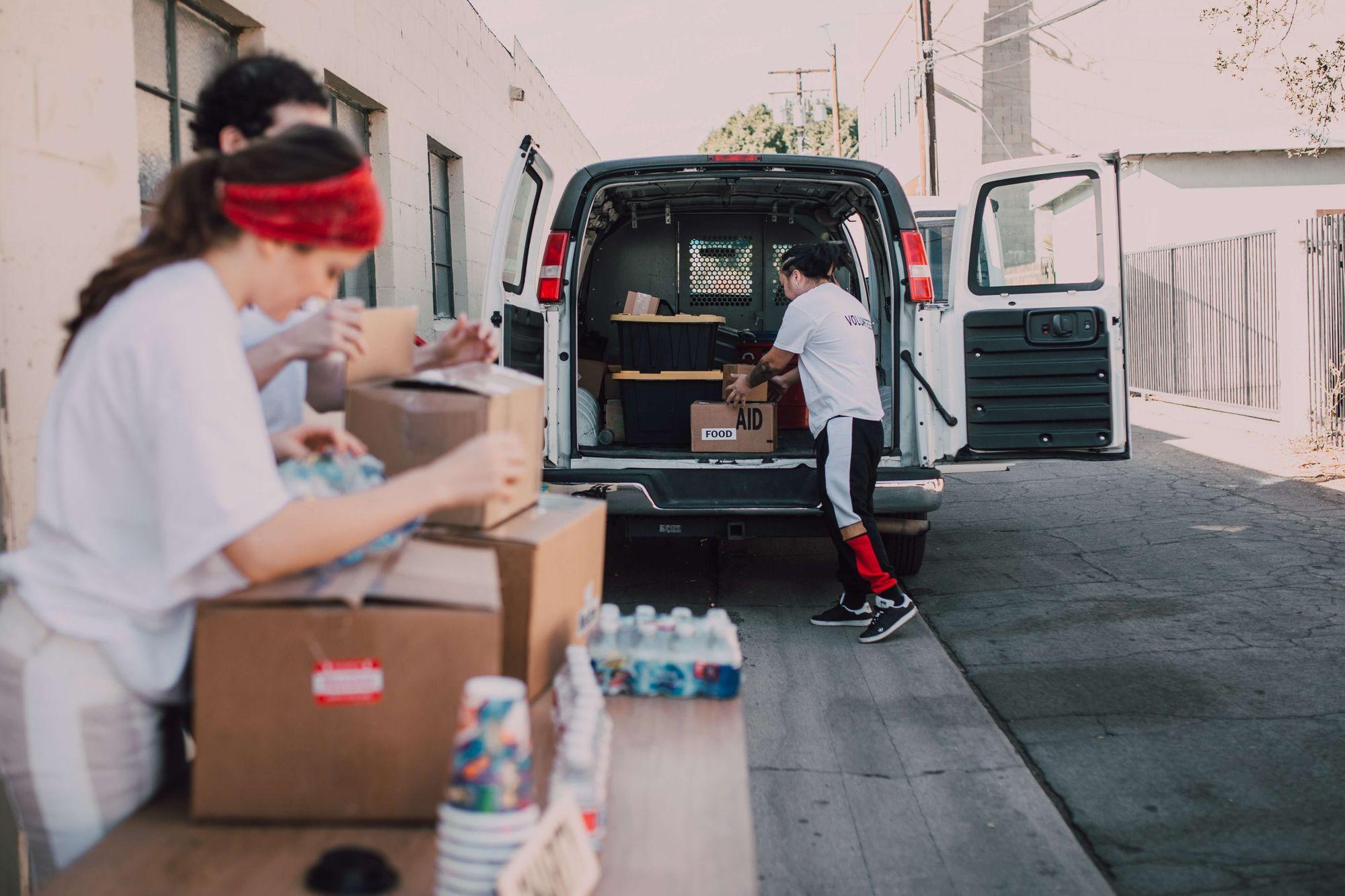 Foto mostra voluntários retirando suprimentos de van parada em rua tranquila. Em destaque, um voluntário homem está tirando caixas do porta-malas do veículo. Ao lado esquerdo da foto, de forma desfocada, aparecem uma voluntária mulher e um voluntário homem, que estão abrindo caixas em cima de mesa.